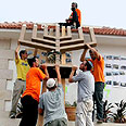 Lowering a Menora from the synagogue in Netzarim Photo: Reuters