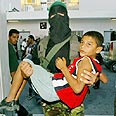 Hamas terrorist carrying wounded boy from scene Photo: Reuters