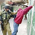 Soldier arrests wanted Palestinian in Hebron Photo: Reuters