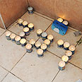 Memorial candles spelling out 'Regev's name in Hebrew Photo: George Ginsberg