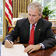 Bush signs bailout bill Photo: AFP