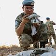 UNIFIL soldier examining rocket Photo: Hagai Aharon