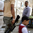 Palestinian gunman returns weapon (archives) Photo: AP