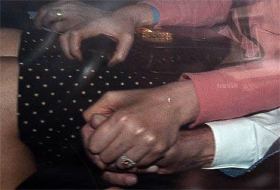 דנג ומרדוק אוחזים ידיים לאחר השימוע, במכונית (צילום: AFP)