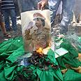Burning Qaddafi's poster Photo: AFP
