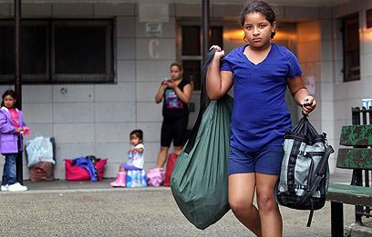 ילדה מתפנה מביתה בניו יורק. 100 מקלטים למפונים (צילום: AFP)