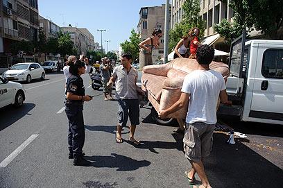 גם את הספה לקחו לפעילים. פורקים את המשאית ברחוב (צילום: בן קלמר)