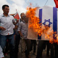 An Israeli flag is burned in riots near Ramallah Photo: Reuters