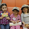 Eden, Mia and Hila proudly display handmade menoras from local Jewish day schools in US Photo: Yonit Schiller, courtesy of Nefesh B'Nefesh