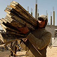Palestinian laborer carries wood planks at UN-funded construction site in Rafah Photo: Reuters