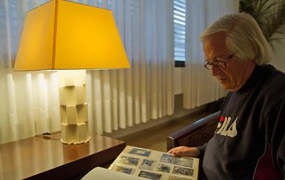 רני סוסקין עם אלבום תמונות שצילם סבו עם הרוליפלקס (צילום: יניב ברמן)