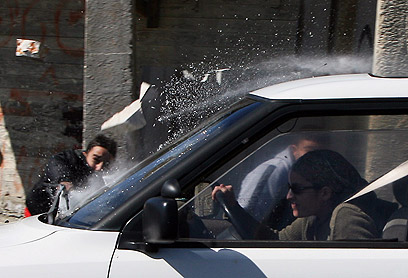 Palestinian boy throws brick at car in West Bank (Archive photo: AFP)