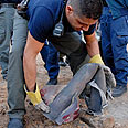 Policeman picking up empty shell of Qassam rocket Photo: Amir Cohen
