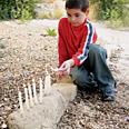 Child lights Hanukkah menorah