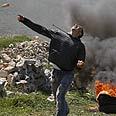 Palestinian hurling stones, Saturday Photo: AFP