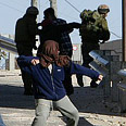 Soldiers and settler youths in Hebron Photo: Reuters