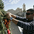 A Palestinian prepares Christman decorations. Church of the Nativity is seen in the background Photo: AFP