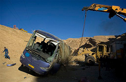 Workers remove the destroyed bus (Photo: AP)