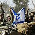 Soldiers wave Israeli flag in Gaza Photo: Reuters