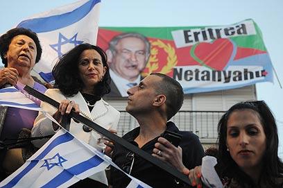 """ח""""כ רונית תירוש על בימת העצרת, ומאחוריה כרזה נגד נתניהו (צילום: ירון  ברנר)"""