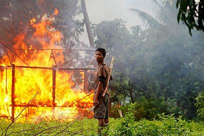 הבודהיסטים הלאומנים רודפים אחר מוסלמים ושורפים את בתיהם (צילום: רוטרס)