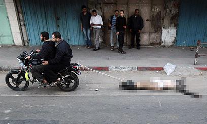 """גופת אחד מ""""משתפי הפעולה"""" נגררת ברחוב (צילום: רויטרס)"""