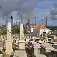 Beth Haim cemetery, backdropped by Isla oil refinery Photo: AP