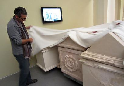 אחד מאוצרי התערוכה מסיר הכיסוי מעל הסרקופגים של הורדוס (צילום: דני הרמן)