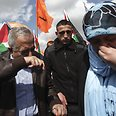 Fayyad tries to cover his face to avoid tear gas Photo: EPA