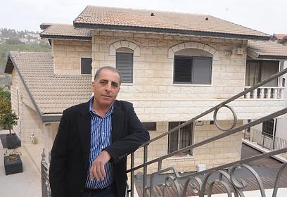 כאמל שגראוי על רקע ביתו (צילום: אביהו שפירא)