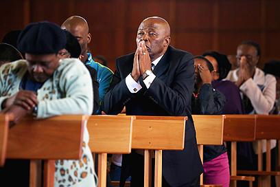 """מתפללים לשלומו של """"מדיבה"""" בכנסייה ביוהנסבורג (צילום: Gettyimages)"""