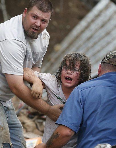 אב מחלץ את בנו מהריסות בית הספר שנפגע בסופה (צילום: AP)