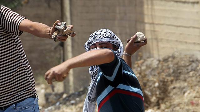 Palestinians throwing stones near Hebron (Photo: EPA)