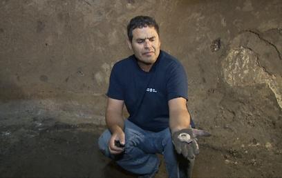 הארכיאולוג אלי שוקרון מציג את המנורה הזעירה (צילום: אלי מנדלבאום)