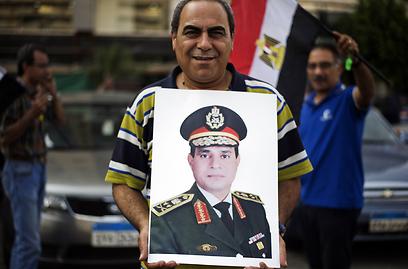 אזרח מצרי מניף את כרזת הגנרל סיסי, מפקד הכוחות המזוינים (צילום: AFP)