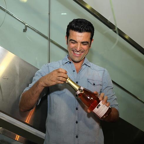 עמוס פותח את השמפניה. יש לו סיבות (צילום: איציק בירן)