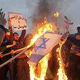 Students burn Israeli flag in Iran Photo: EPA