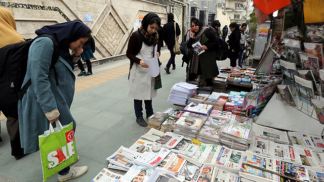 Iranians look at newspapers after signing of nuclear deal (Photo: EPA)