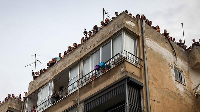 אנשים התקהלו על הגגות מסביב לבית העלמין (צילום: אבישג שאר-ישוב)