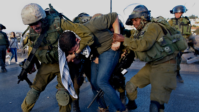 IDF soldiers restraining a man at a protest in West Bank (Photo: AP)