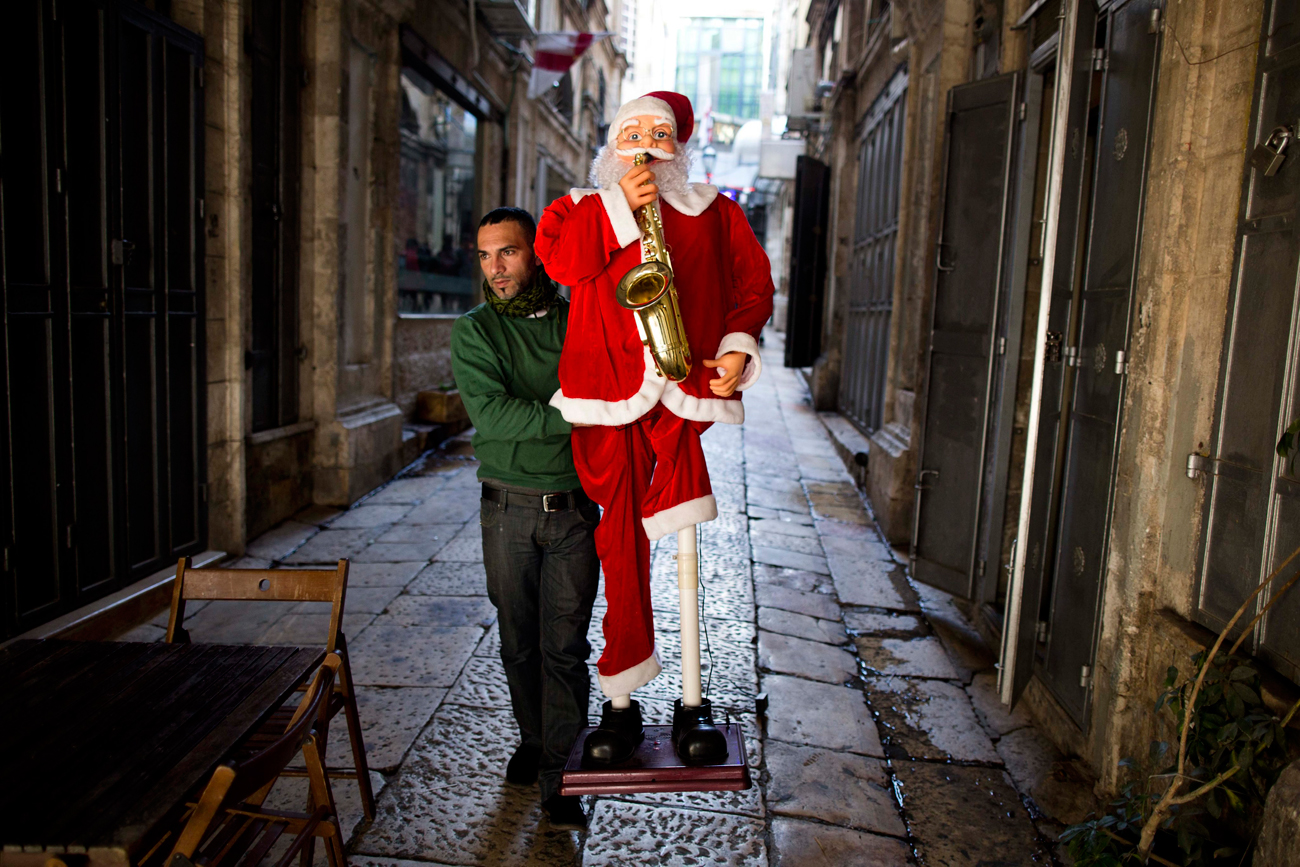 Palestinian carries a Santa in the Old City of Jerusalem (Photo: EPA)
