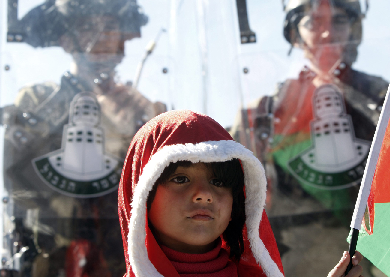 Palestinian child dressed as Santa stands by Border Police officers during protest near Bethlehem (Photo: AP)