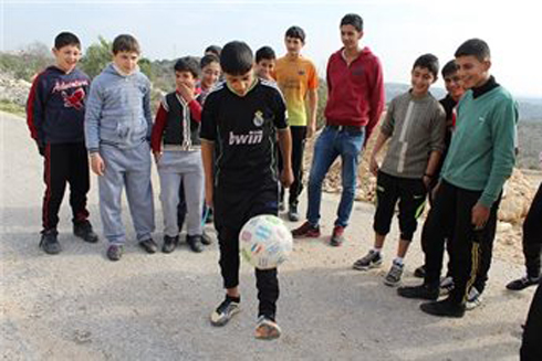The children playing with a replacement ball (Photo: Ma'an)