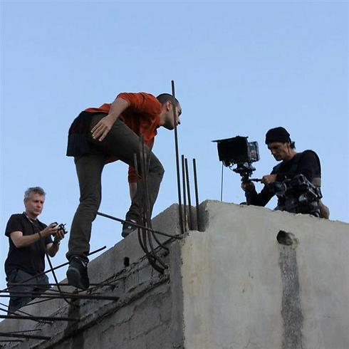 חיים אסיאס מצלמים על גגות הבתים במחנה הפליטים ()