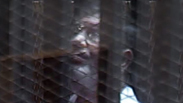 Egypt's deposed President Mohammed Morsi behind bars Photo: AP