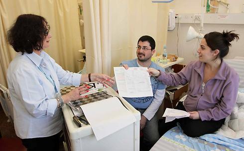 ההורים הטריים איתמר ואסנת מקבלים את הטופס מציפי שני (צילום: עידו ארז)