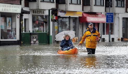 מפלסת את דרכה עם עזרה מחבר. פינוי אישה מבוגרת בברקשייר (צילום: EPA)