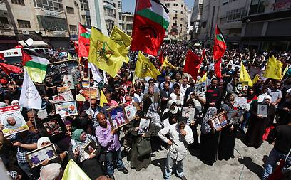 Families holding pictures of prisoners in Ramallah rally (Photo: EPA)