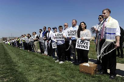Mourners displaying anti-hate signs at the funeral (Photo: Reuters)