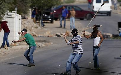 Palestinians hurl stones at Israeli security forces in Silwad (Photo: AFP)